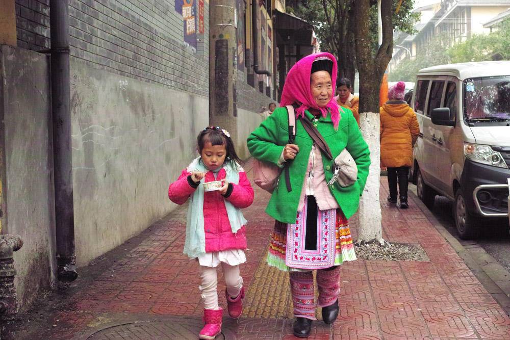 黔西南,奶奶接孙女放学回家,孙女捧着路边摊买的小吃.