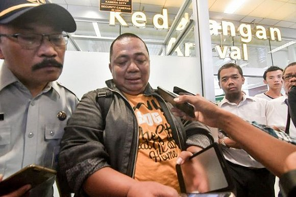 Sony Setiawan (C) speaks to journalists at Pangkal Pinang airport in Bangka Belitung province on October 29, 2018, following his arrival on another airline after missing his pre-planned flight on Lion Air flight JT 610 which crashed off the coast north of Jakarta. - Setiawan was due to board the ill-fated Boeing-737 MAX but was held up on his commute to Soekarno-Hatta airport by Jakarta's notorious traffic congestion. The brand new Indonesian Lion Air plane carrying 189 passengers and crew crashed into the sea on October 29, officials said, moments after it had asked to be allowed to return to Jakarta. (Photo by RONI BAYU / AFP).