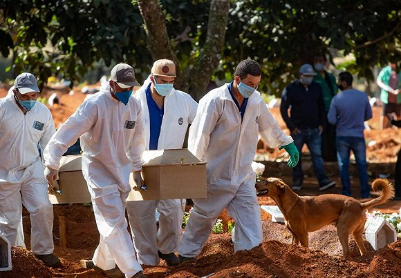 Cemetery workers in protective clothing carry a coffin (AAP)